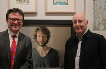 Thumbnail image of Chris Hailes of Charles Stanley with Geoffrey Beasley in front of 'Portrait of Alex' - LSA Annual Exhibition 2017 Prize Winners