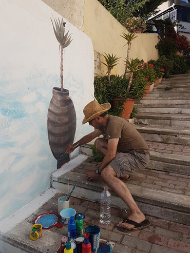 Thumbnail image of George Sfougaras painting a mural in Potamies - Art Abroad - George Sfougaras Paints In Potamies