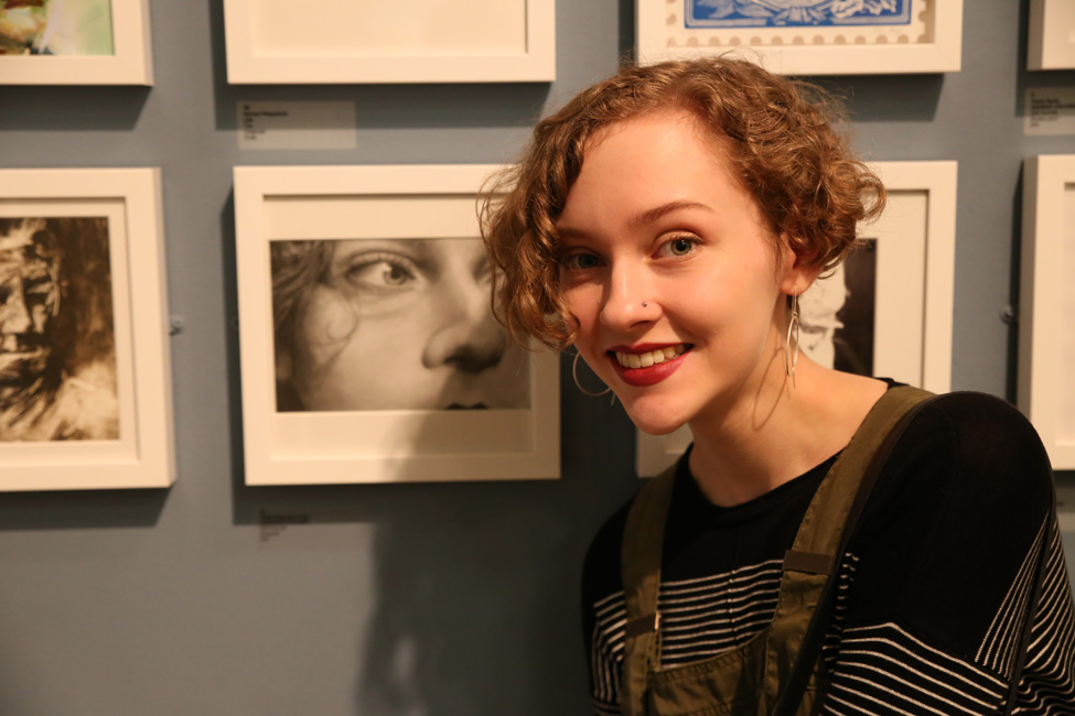 Thumbnail image of Orlan Sharman-Dunn, Leicester College student, in front of her self portrait - Little Selves - Preview Photographs