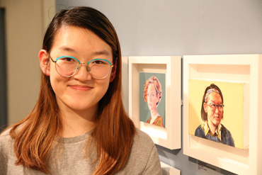 Thumbnail image of Yuanqing Zhang (Leicester High School for Girls student) in front of her prize-winning oil painting,'Self portrait' - Little Selves - Preview Photographs