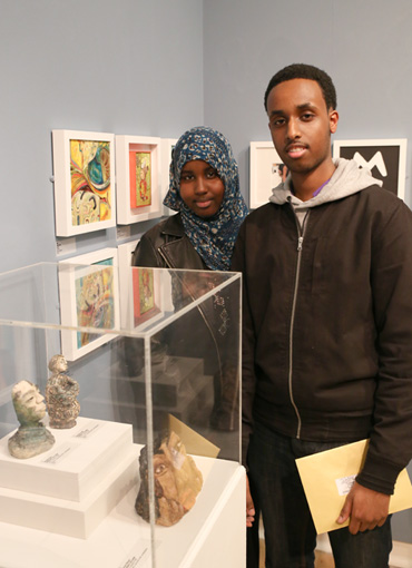 Thumbnail image of Nooridin Abdi (Gateway college student) with his sister, his prize winning 'Ceramic Little Self' is in the cabinet - Little Selves - Preview Photographs