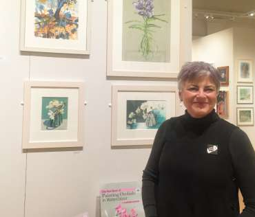 Thumbnail image of Vivienne Cawson in front of two her orchid paintings - Meet the LSA Artists at New Walk Museum!
